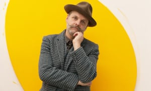 Gavin Turk in a checked jacket and trilby with a yellow oval shape on the wall behind him