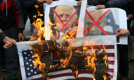 Palestinians burn posters depicting Donald Trump and Benjamin Netanyahu during a protest against the US intention to move its embassy to Jerusalem and to recognise the city as the capital of Israel, in Rafah in the Gaza Strip.