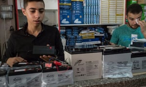 Staff in Imad Shlayl's electronics shop in Gaza City test a battery storage system