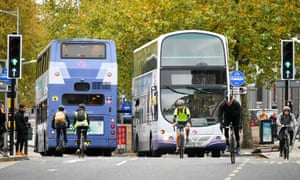 Cyclists and buses in Bristol city centre.