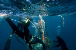 Divers ensure the sculpture makes a safe descent