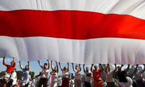 Opposition supporters wave a huge old Belarusian national flag as they rally in the center of Minsk, Belarus.