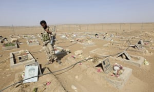 A soldier stands next to graves of Houthi fighters in Yemen