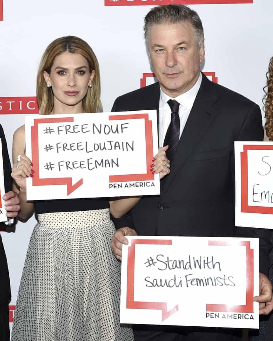 Actor Alec Baldwin and his wife, Hilaria, pose holding signs in support of jailed Saudi women's rights activists at the 2019 PEN America literary gala in New York