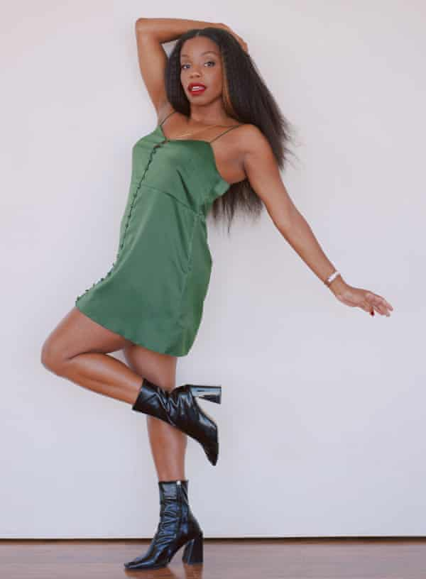 London Hughes in a short green strappy dress and black heeled boots