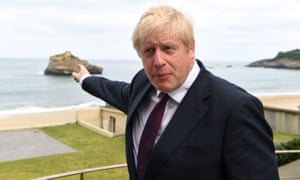 Boris Johnson points to the rock he swam to off Biarritz.