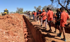 Students from Yiramalay School and community members sprinkle pindan dirt over the remains.