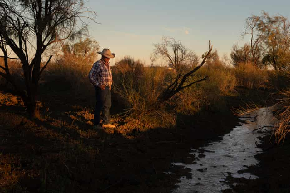 Dude Kidd watches as water from rains slowly runs down a gully on his property