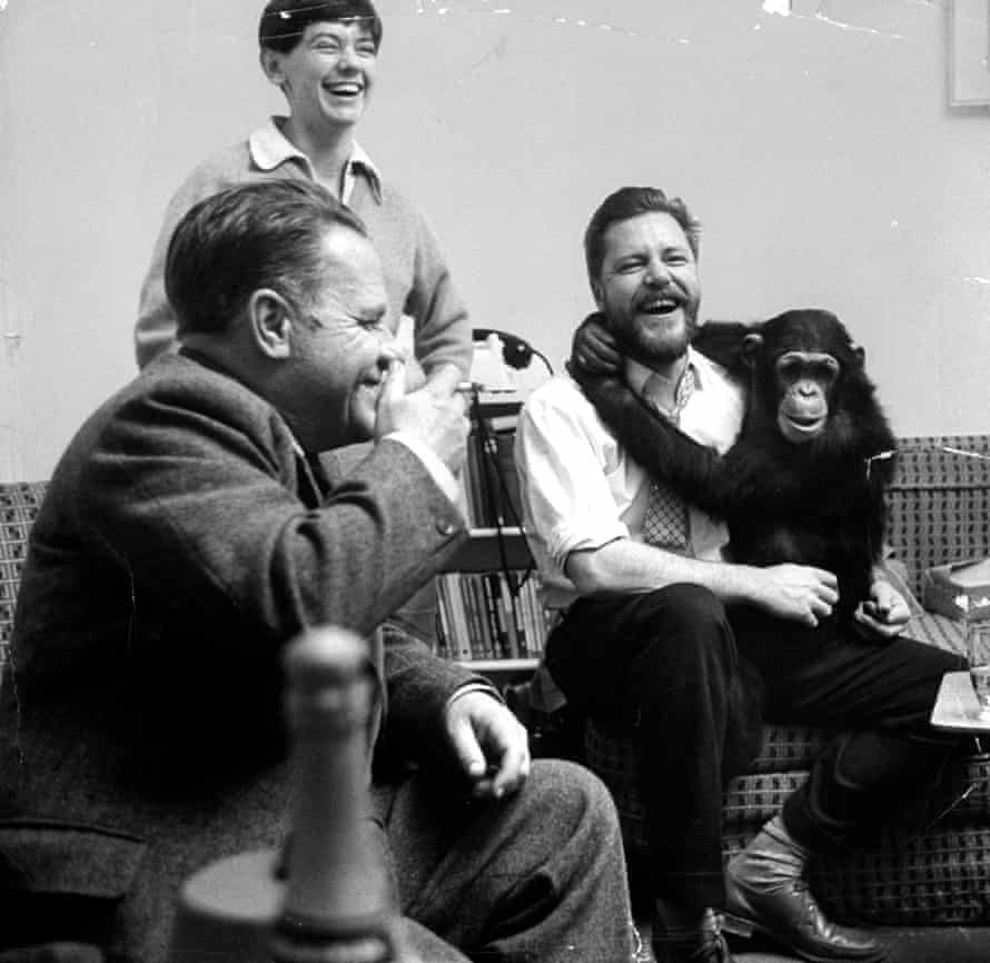 Gerald Durrell holding his pet chimpanzee and talking with his brother, novelist Lawrence Durrell, left, at his home on Jersey in 1961.
