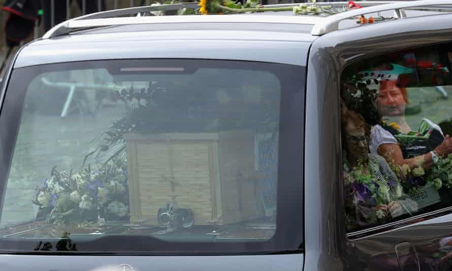 People are reflected in the glass of the hearse in Batley.