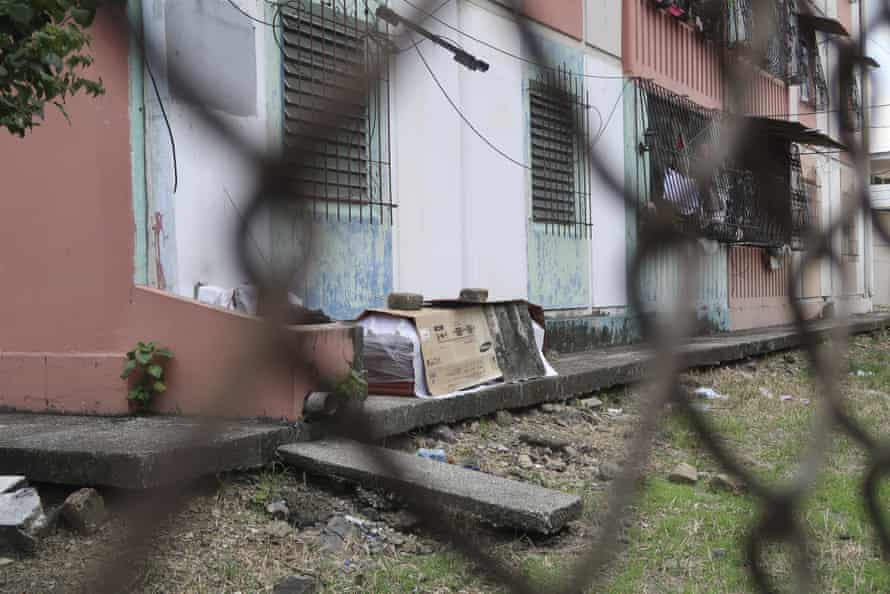 A coffin with the body of a person who is believed to have died from Covid-19 lies wrapped in plastic and covered with cardboard, outside a block of family apartments in Guayaquil.