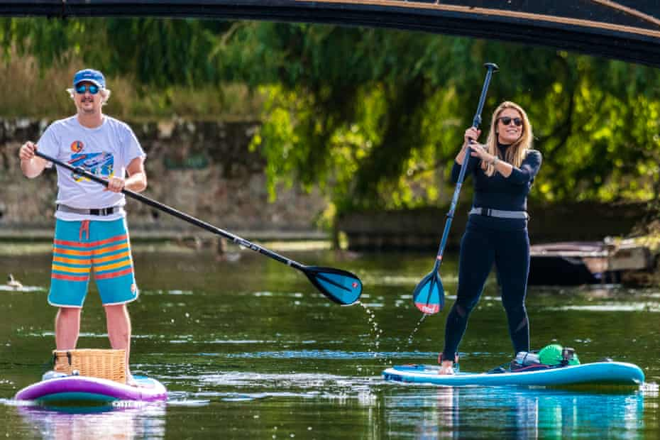 Adam Partington and Gemma Cann paddleboarding in Cambridge.