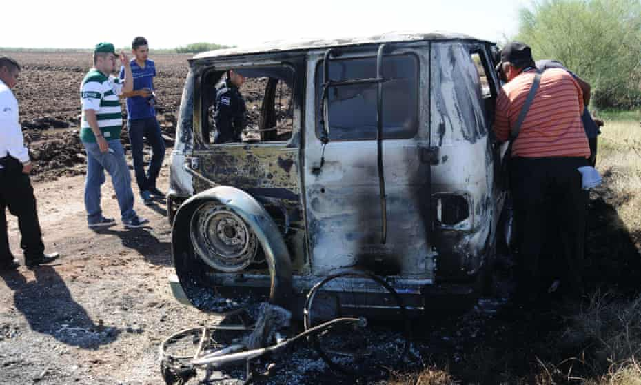 Forensic personnel inspect the burned-out van in which two Australian citizens were allegedly travelling through Sinaloa state.