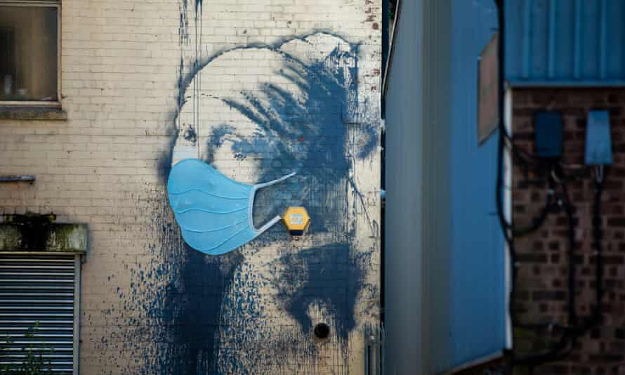 Banksy's The Girl with a Pierced Eardrum in Hanover Place Bristol, with the addition of a medical facemask.