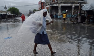 A woman in Port-au-Prince protects herself from the first rains brought on by Hurricane Matthew.