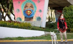 A woman and her dog are pictured in front a mural in honor to health workers as the coronavirus outbreak continues, in Mexico City, Mexico 7 November 2020.