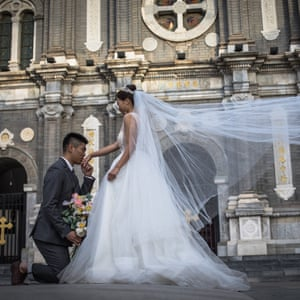 A couple pose for their pre-wedding photos on a street in Beijing