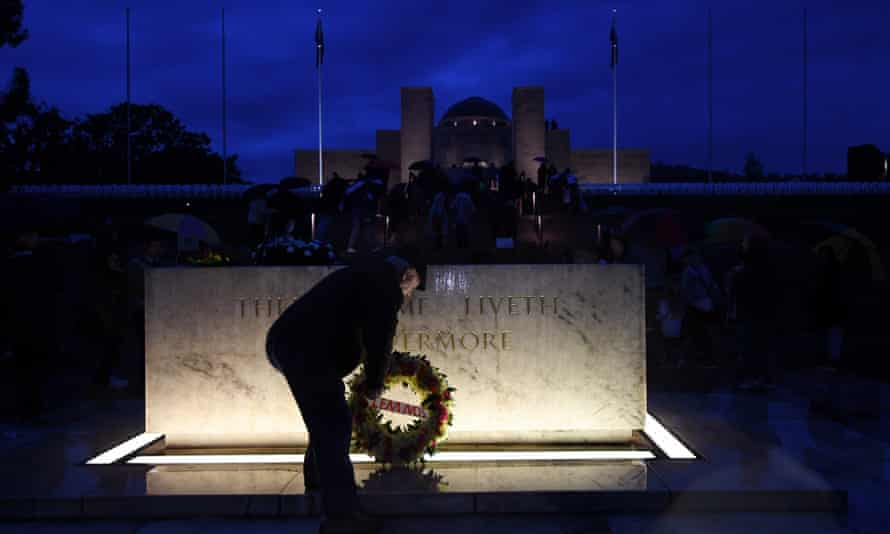 a man leaves a wreath at the stone of remembrance in front of Canberra's war memorial