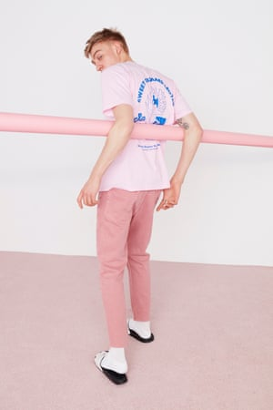 Pink T-shirt with blue graphics at the back, black and white sliders, dusty pink jeans