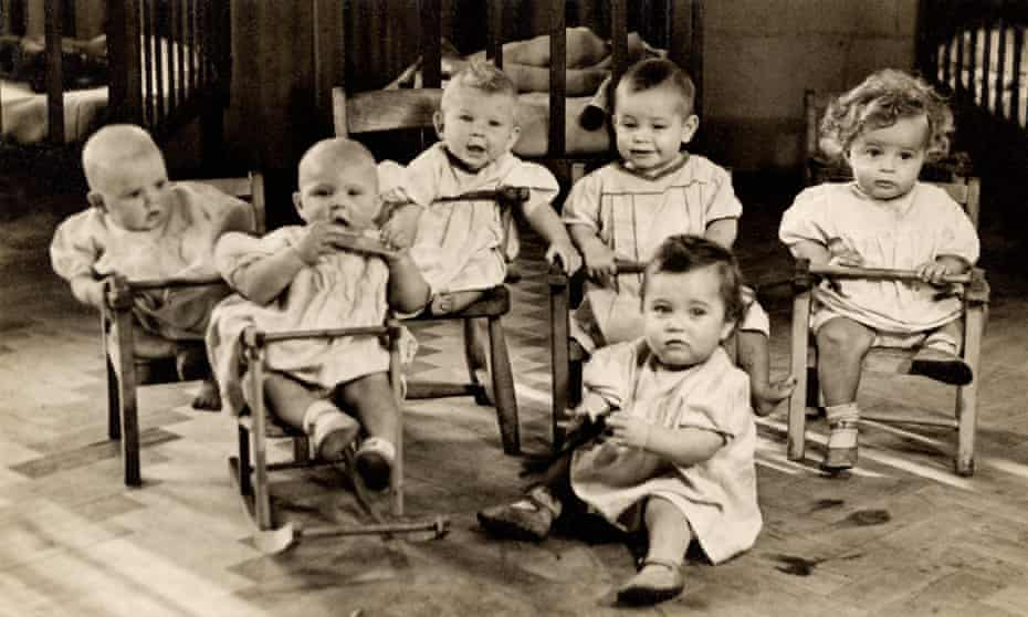 Babies in a nursery in East London in the early 1900s, possibly in a Barnardo's orphanage or hospital ward.