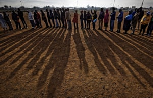 People queue in the early morning sun in the mining settlement of Bekkersdal, west of Johannesburg