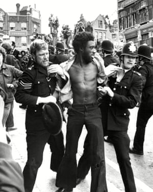 A man is held by police in the Lewisham demonstrations. A total of 214 people were arrested.