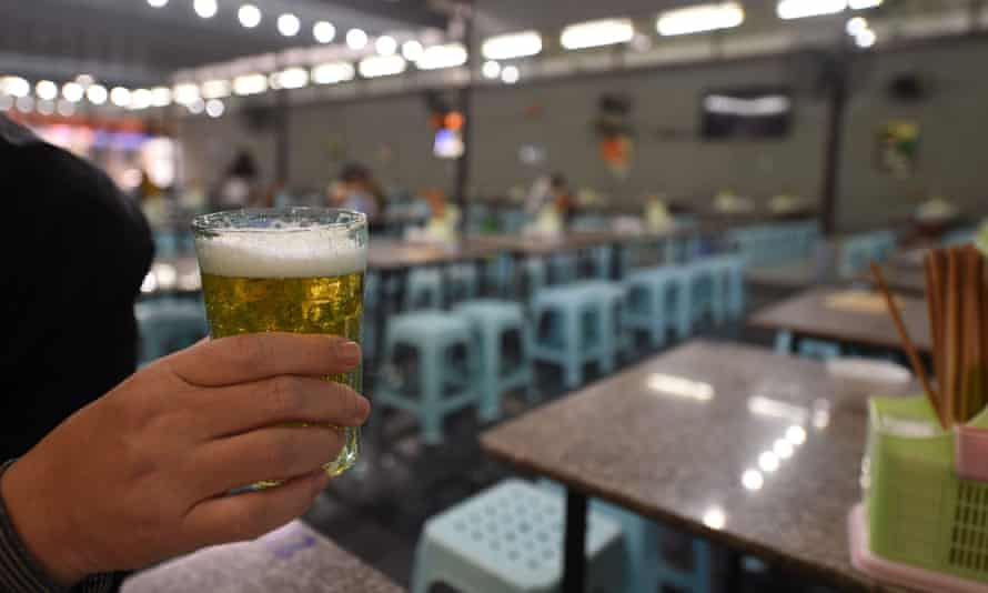 A diner holds a glass of beer at a bar in Hanoi