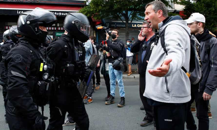 A demonstrator argues with police at an anti-Covid rules protest in Paris