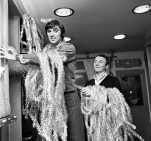 """George Best and Mike Summerbee get the tinsel out as they decorate their fashion boutique """"Edwardia"""" in 1967"""