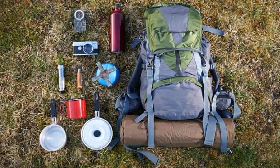 A backpack and camping gear laid out on the grass.