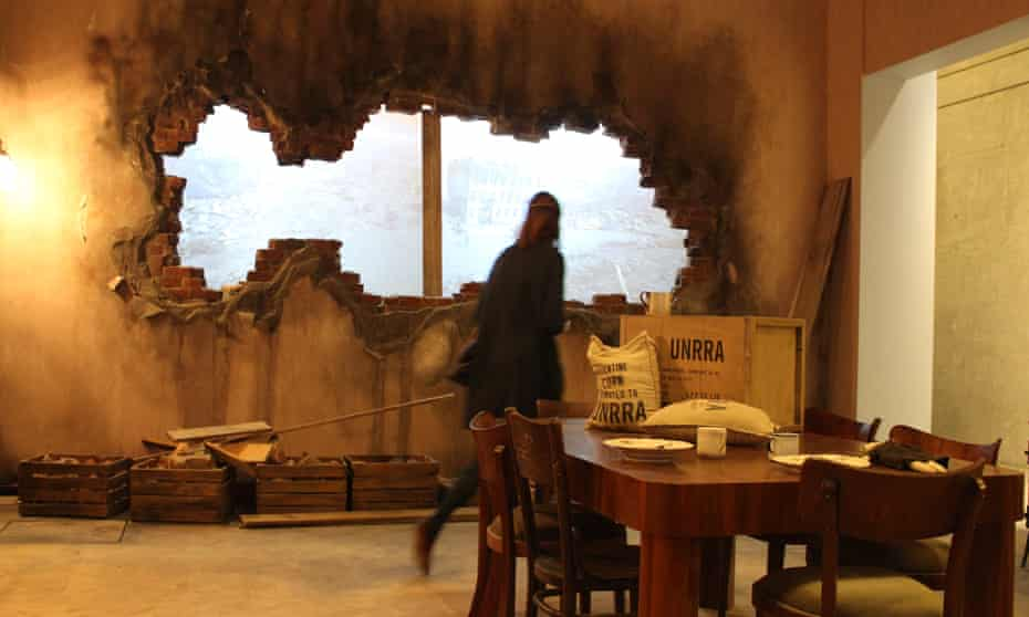 A woman walks around a display at Gdansk's second world war museum, the wall in front of her has been destroyed to look like a bombshell has hit it, and there is a view to what would be the outside.