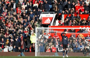 David De Gea and fans shelter their eyes from the sun.