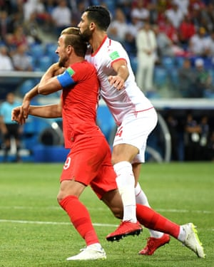 Harry Kane of England and Yassine Meriah of Tunisia clash in the penalty area.