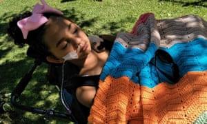 Electric shock victim Denishar Woods lies in a wheelchair