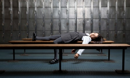 A young girl asleep on a bench in a locker room