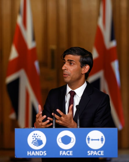 Rishi Sunak at a podium giving a briefing, with two union jacks in the background.
