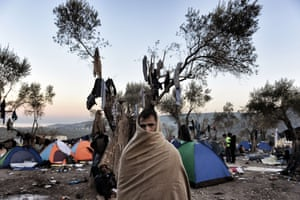 A man stands near tents where refugees and migrants live in a field outside the Moria registration centre on the island of Lesbos