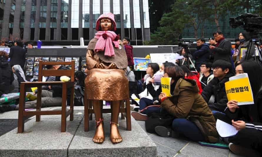 South Korean protesters sit near a statue of a teenage girl symbolising former 'comfort women', who served as sex slaves for Japanese soldiers during the second world war