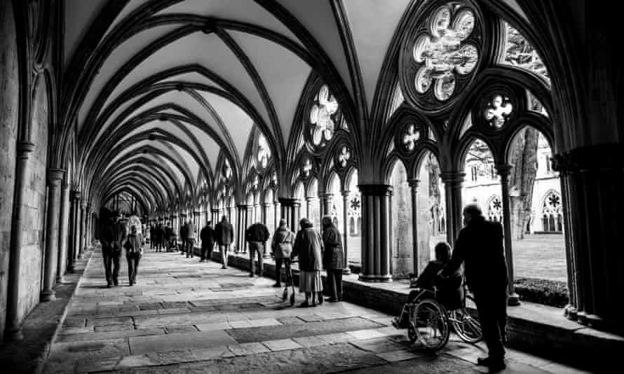 A high-contrast black and white photo looking down a long cloister at the cathedral, with a queue of socially distanced people waiting