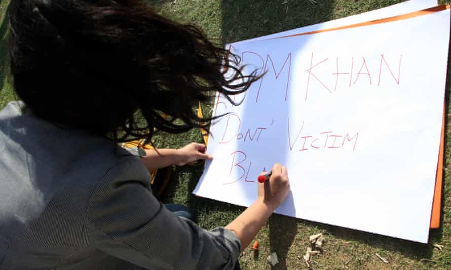 An activist of Pakistani rights groups prepares a placard during a protest against Prime Minister Imran Khan's remarks on the reasons of rising in rape cases