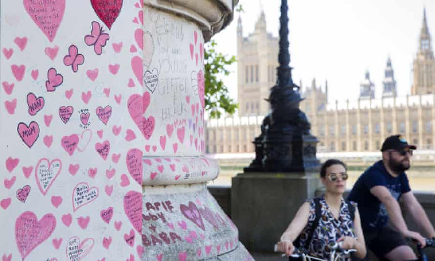Pedestrians walk past the national Covid memorial wall in central London.