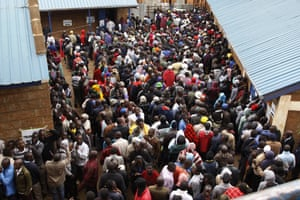 Voters line up early morning in cold weather at a polling station in the Kibera Slums