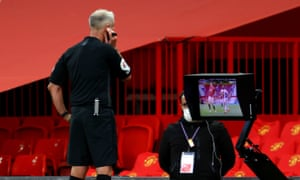 Martin Atkinson consults the monitor before giving a penalty to Crystal Palace for handball by Manchester United's Victor Lindelöf.