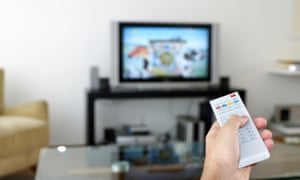 Man watching TV, focus on hand holding remote control