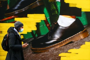 """A shopper walks past the window of a """"Dr Martens"""" shoe shop amid the coronavirus disease (COVID-19) outbreak in central Madrid."""