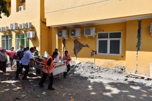 A man is wheeled passed a damaged wall to the makeshift ward set up outside a hospital