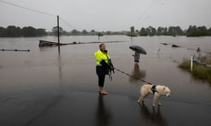 Locals inspect the floodwaters where the Hawkesbury River has broken its banks at Pitt Town, NSW on 23 March 2021.