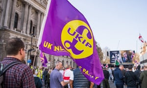 A Leave supporter carries a Ukip flag with a large pound sterling logo on a march in Whitehall.