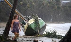 A local resident walks past a yacht washed ashore at Airlie Beach