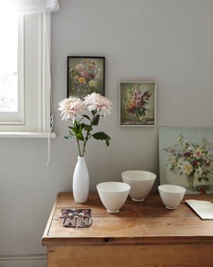 A wooden chest in the simple spare room has vintage flower pictures mixed with ceramics found in South Africa.